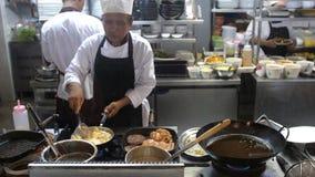 Koh Samui, Tailândia, 20 pode abril de 2018 O cozinheiro chefe profissional cozinha costoletas com alimento triturado das agitaçõ Imagens de Stock