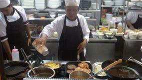 Koh Samui, Tailândia, 20 pode abril de 2018 O cozinheiro chefe profissional cozinha costoletas com batatas trituradas em uma band Imagens de Stock