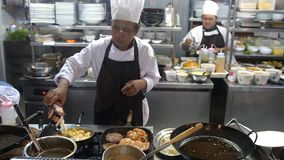 Koh Samui, Tailândia, 20 pode abril de 2018 O cozinheiro chefe profissional cozinha costoletas com batatas trituradas em uma band Foto de Stock