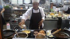 Koh Samui, Tailândia, 20 pode abril de 2018 O cozinheiro chefe profissional cozinha especiarias dos addes das costoletas em batat Fotografia de Stock Royalty Free