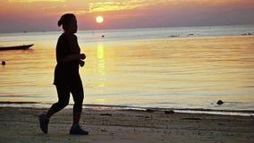 Koh Samui, Thailand, 3 april 2016. Thai woman runs along a tropical beach during an amazing sunset. slow motion. Thai woman runs along a tropical beach during an stock footage