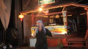 KOH SAMUI, THAILAND 25 JULI 2014 De vrijwilliger zingt stock footage