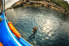 Scuba diver jump into water with wide step from boat. KOH TAO, THAILAND - 26. MARCH 2018. Scuba diver jump into water with wide step from boat. Day editorial stock image