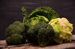 Kohl, Blumenkohl, Brokkoli auf schwarzem Hintergrund Stockfotografie