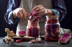 Kohl kimchi im Glasgefäß Frau, die purpurrotes Kohl- und Wassermelonenrettich kimchi vorbereitet Gegorene und vegetarische probio stockfoto