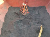 Kohle, die Operation durch das Zupacken und den Bagger des Kranes auf Massengutfrachter entlädt stockbild