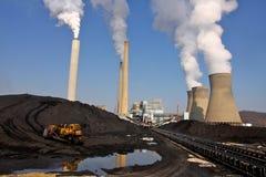Kohle geanhäuft vor brennender Triebwerkanlage der Kohle stockfotos