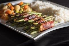 Kohlenhydratarm - die grünen Bohnen, die in Speck woth eingewickelt wurden, mischten Gemüse und Reis auf weißer Platte Lizenzfreie Stockbilder