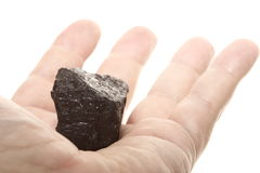 Kohlenklumpen-Kohlenstoffnugget in der männlichen Hand lokalisiert Lizenzfreie Stockfotos