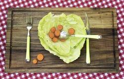 Kohlplatte mit Karotte und Löffel in ihm Lizenzfreies Stockbild