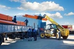 Kohonovo,白俄罗斯- 2017年10月29日, :卡车和人装载堆户外黑pvc塑料管子仓库外 库存图片