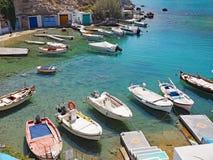 Kojor för fiskare` som s sneds in i den steniga kusten, och fartyg förtöjde på Milos Island Royaltyfria Bilder