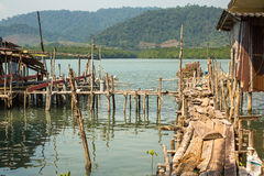 Kojor och fiskebåt på pir in på fiskarebyn Arkivbilder