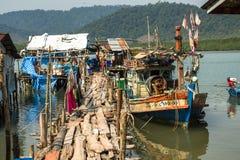 Kojor och fiskebåt på pir in på fiskarebyn Arkivfoton
