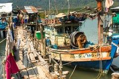 Kojor och fiskebåt på pir in på fiskarebyn Arkivfoto