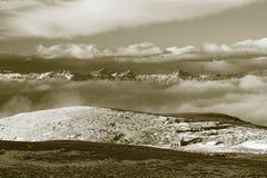 Kojor på maxima av fjällängkullen, skarpa steniga berg på horisonten Solig vinterdag Djupfryst stjälk av gräs i stor äng med nytt Fotografering för Bildbyråer