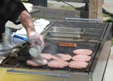 Kok Adding Salt aan Burgers-het koken bij de grill stock afbeelding