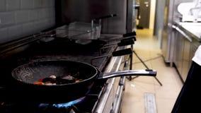 Kok bradende zeevruchten en garnalen in restaurantkeuken stock footage