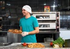 Kok die bij lijst een verse pizza voorbereiden Royalty-vrije Stock Fotografie