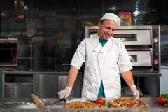 Kok die bij lijst een verse pizza voorbereiden Royalty-vrije Stock Foto