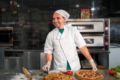 Kok die bij lijst een verse pizza voorbereiden Royalty-vrije Stock Foto's