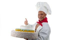 Kok die de jonge mens en een grote cake glimlachen stock foto