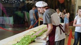 Kok die de langste sandwich maken stock video