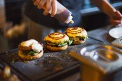 Kok die hamburger voorbereiden die de saus op de roomkaas toevoegen stock fotografie