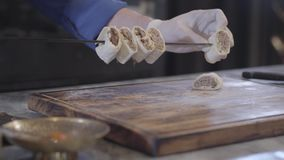 Kok die die kebabstukken vastbinden in pitabroodje lavash op vleespen dichte omhooggaand worden verpakt Succesvolle mens het koke stock videobeelden