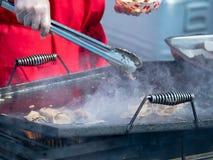 Kok die met tang stukken van varkensvlees op een rooster wegknippen royalty-vrije stock foto's