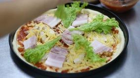 Kok die pizza voorbereidt laag van sla stock video