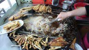 Kok die verse vissen op een grote pan braden bij de box in Istanboel Turkije stock footage