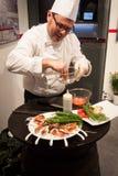 Kok die vingervoedsel voorbereiden bij Beetje 2014, internationale toerismeuitwisseling in Milaan, Italië Stock Fotografie