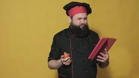 Kok in een zwart kostuum op een gele achtergrond stock videobeelden