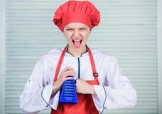 kok in eenvormig restaurant, meisje in schort en hoed Professionele Chef-kok Cooking in Keuken de boze vrouw houdt van kokend voe stock afbeeldingen