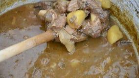 Kok het bewegen met houten lepel traditionele hutspot in ketel Stovende vlees en groenten in geëmailleerde ketel in tuin op de zo stock videobeelden