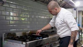 Kok in het bradende vlees van de restaurantkeuken op fornuis op een pan stock video