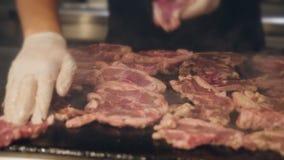 Kok het roosteren stukken van vlees op een grote grill in het restaurant De kok draait de vleesstukken op de grill stock footage