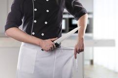 Kok met mes, vooraanzicht met keuken op achtergrond het 3D teruggeven en foto Hoge Resolutie Royalty-vrije Stock Foto's