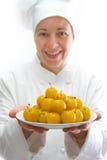 Kok met schotel van gele pruimen Royalty-vrije Stock Afbeeldingen