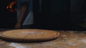 Kok in schort die hete en hete pizza nemen uit oven Stock Afbeeldingen