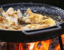 Koka i olja på öppnad brand som steker fiskfilén Fotografering för Bildbyråer