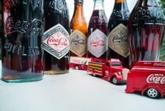Koka-kola rocznika pojazdy i stare butelki obraz stock
