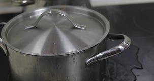 Koka vatten i pannan som t?ckas med ett lock i k?ket royaltyfri bild