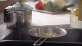 kokande pasta Tömning av makaronivatten till och med en durkslag i vasken arkivfilmer