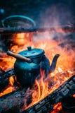 Kokande vatten för gammal Retro järnlägerkokkärl på en brand i skog Arkivfoton