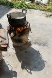 kokande vatten för svart kruka för att laga mat på den avfyrade ugnen bredvid f Arkivfoto