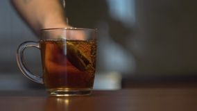 Kokande vatten hälls in i en råna med en tepåse stock video