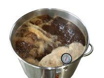 Kokande Wort för hem bryggat brunt öl på vit bakgrund arkivbild