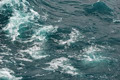 Kokande yttersida av vatten under påverkan av stark vind Färgstänk och droppar av vatten sprider i olika riktningar Fotografering för Bildbyråer